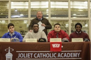 (Lathan Goumas – lgoumas@shawmedia.com) Head coach Dan Sharp talks about Bradley Krisch (from left), Kenneth Aguirre, Tyler Witt and Ze'veyon Furcron as they prepare to commit to NCAA Division One schools Wednesday during a National Letter of Intent Signing Day event at Joliet Catholic Academy in Joliet. Twelve total students signed letters of intent to compete in collegiate athletics.